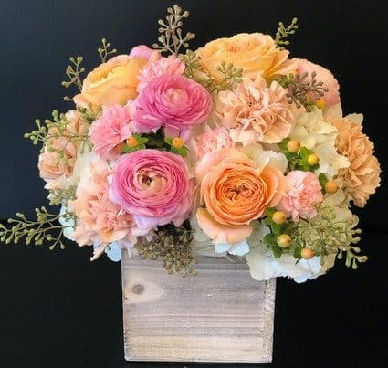 A lush design of pink, peach and white flowers in a wood box